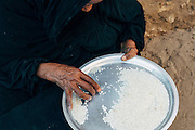 Old nubian woman refining rice. They get this rice among other subsidized supplies