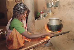 Indian girl affected by polio; member of selfhelp group supported by the charity ADD India; cooking in family home,