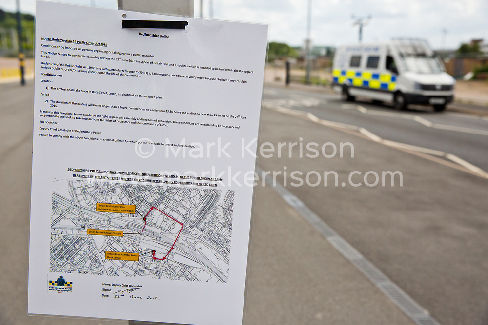 Luton, UK. 27th June, 2015. A notice under Section 14 of the Public Order Act 1986 posted by Bedfordshire Police to impose restrictions on a march by far-right group Britain First. A large police presence kept supporters of Britain First and Unite Against Fascism apart.