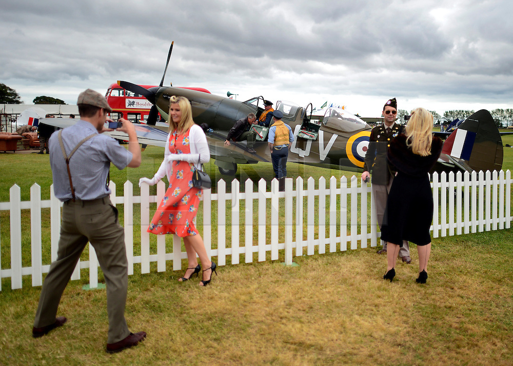 © Licensed to London News Pictures. 16/09/2012. Goodwood, UK . People take photographs whislt Spitfire pilots take a break from display flying on the wings of their aircraft. People enjoy the atmosphere at the 2012 Goodwood Revival. The event recreates the glorious days of motor racing and participants are encouraged to dress in period dress. Photo credit : Stephen Simpson/LNP