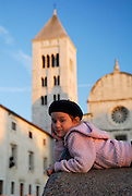 Child (5 years old), resting on wall, Church of St. Mary (Crkva Sveti Marije) in background, in late afternoon sunlight. Zadar, Croatia