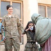 A young girl pours her first bottle of clean water from a filtration system set up by the 2-27's Female Engagement Team (FET) with a translator in a water filtration demonstration in the village of Nari, Kunar Province of Eastern Afghanistan with Waves For Water and the US Military.