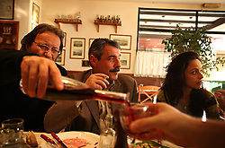 People gather together at a restaurant at the port of Piraeus in Greece on Feb. 20, 2008. Incoming and outgoing ships, as well as shops catering to seafarers, are seen throughout the port.