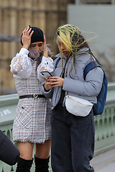 © Licensed to London News Pictures. 01/01/2020. London, UK. Windy weather in the capital as women look at their phone on Westminster Bridge. Photo credit: Dinendra Haria/LNP