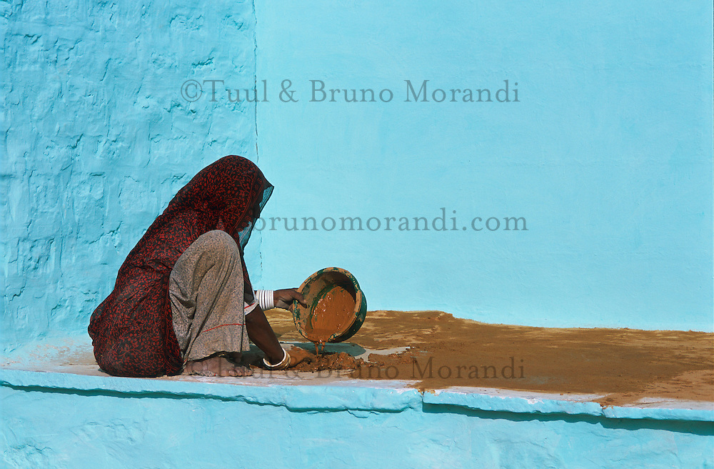 Inde, Rajasthan, Village peint des environs de Barmer, Femme enduisant la terrasse de sa maison. // India, Rajasthan,