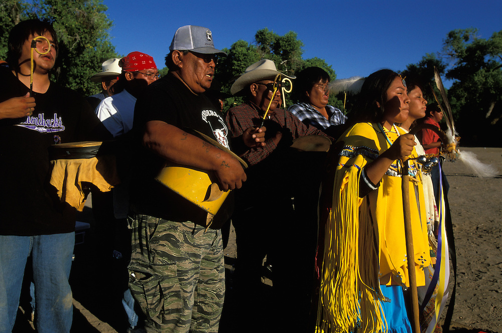 An Apache girl and her helper, both dressed in buckskin dresses, dance at her Sunrise Dance, a first menstruation rite, on the San Carlos Apache Indian Reservation in Arizona, USA. The girl holds a cane that symbolises longevity. Behind her the medicine man and drummers sing and beat their drums. The Sunrise Dance is supposed to prepare the girl for adulthood and to give her a long and healthy life without material wants. The ceremony is also an enactment of the Apache creation myth and during the rites the girl 'becomes' Changing Woman, a mythical female figure, and comes into possession of her healing powers.
