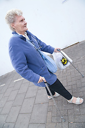 Woman using sticks to help her walk along the pavement during a day trip out organised by the Nottingham Disabled Friendship Club,