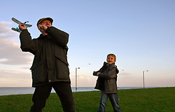 Grandfather and adopted grandson playing with balsa plane UK