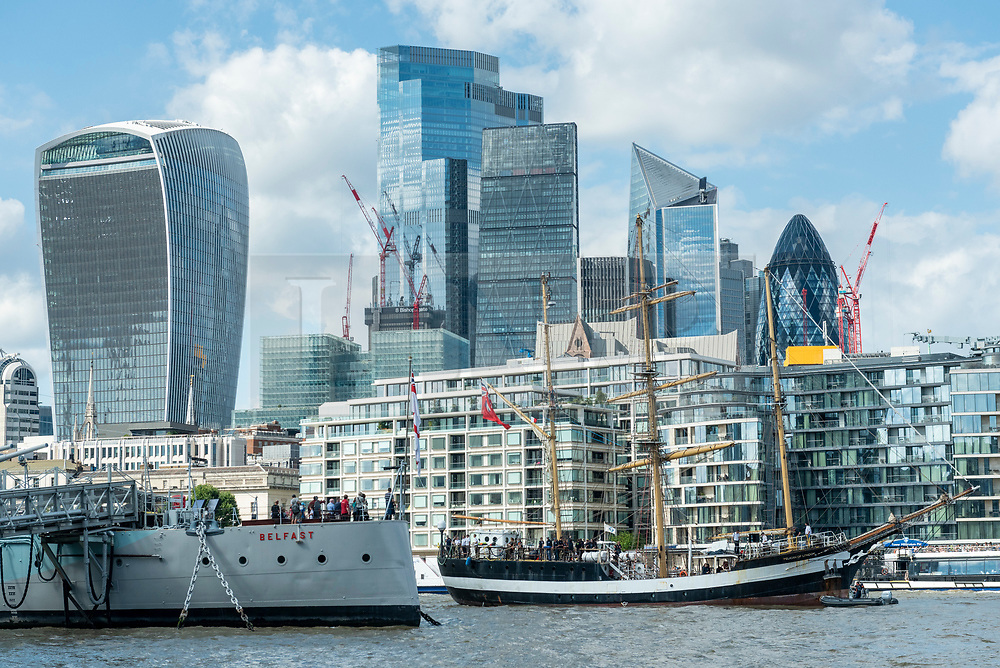"""© Licensed to London News Pictures. 10/08/2021. LONDON, UK.  The tall ship """"Pelican of London"""" in front of the City of London.  Unique among Square Riggers, her hull form was derived from the elite French clippers of the late 19th century, with a length to breadth ratio of 5:1.  She will be moored next to HMS Belfast until 14 August.  TS Pelican is designed principally as a sail training ship but also competes in events worldwide.  Photo credit: Stephen Chung/LNP"""
