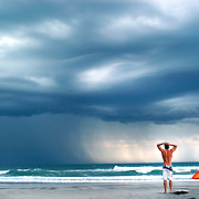 """""""Storm Front Surfers"""" - Surfers watch a storm pass, trying to decide if it was safe to get in the water after there were lightning strikes in the area."""
