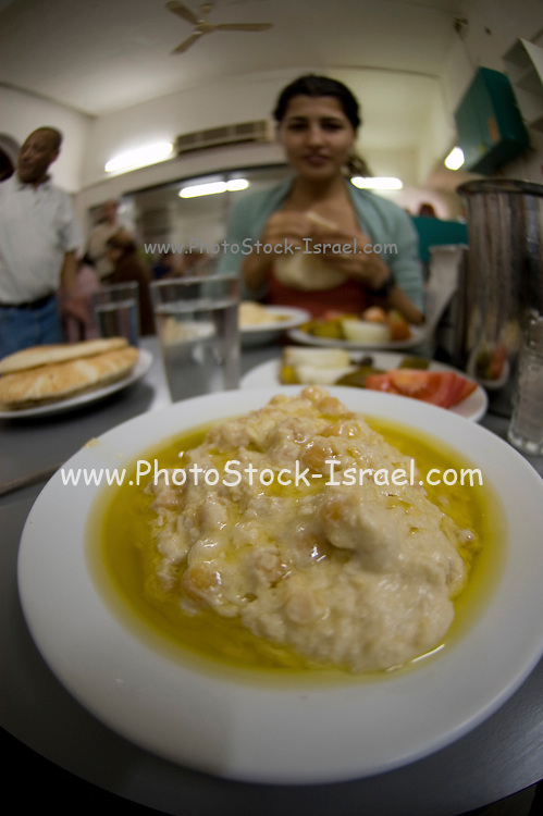 Israel, Western Galilee, Acre, a woman eating humus. Model Release Available