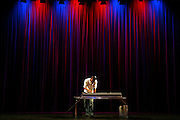 A DJ on a stage with curtains behind at the Stratford Circus Theatre, Stratford, London.