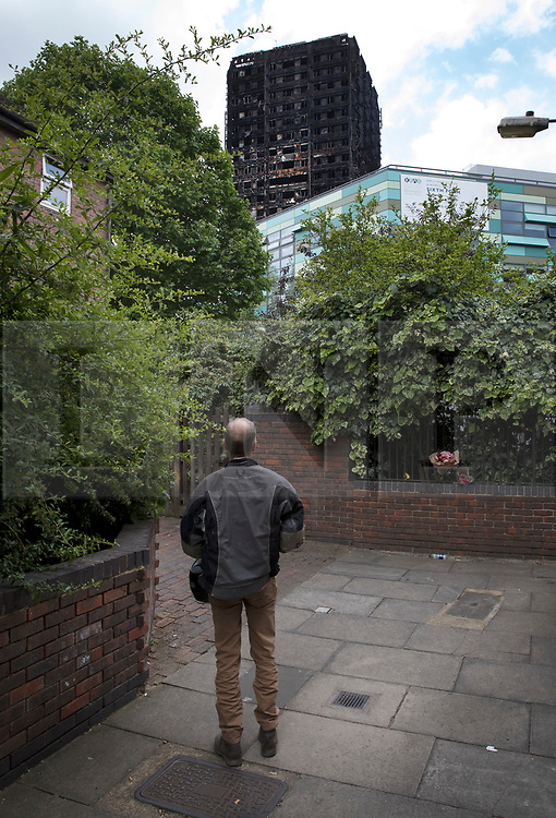 © Licensed to London News Pictures. 18/06/2017. London, UK. A man looks at the remains of the burnt out Grenfell tower block . The blaze engulfed the 27-storey building killing dozens - with 34 people still in hospital, many of whom are in critical condition. The fire brigade say that they don't expect to find anyone else alive. Photo credit: Peter Macdiarmid/LNP
