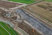 Nederland, Noord-Brabant, Werkendam, 23-10-2013; Ruimte voor de Rivier project Ontpoldering Noordwaard. Voor dit project worden delen van de polder ontpolderd en de dijken worden verlegd en/of verlaagd waardoor bij hoogwater het rivierwater ook door de polder sneller weg kan stromen richting zee. Gevolg van de ingrepen is ook dat de waterstand verder stroomopwaarts zal dalen. Particuliere huzien en boerderijen worden verplaatst naar nieuw opgeworpen terpen.<br /> National Project Ruimte voor de Rivier (Room for the River) By lowering and / or moving the dike of the Noordwaard polder the area will become subject to controlled inundation and function as a dedicated water detention district. Houses and farmhouses will be constructed on new dwelling mounds. <br /> luchtfoto (toeslag op standard tarieven);<br /> aerial photo (additional fee required);<br /> copyright foto/photo Siebe Swart