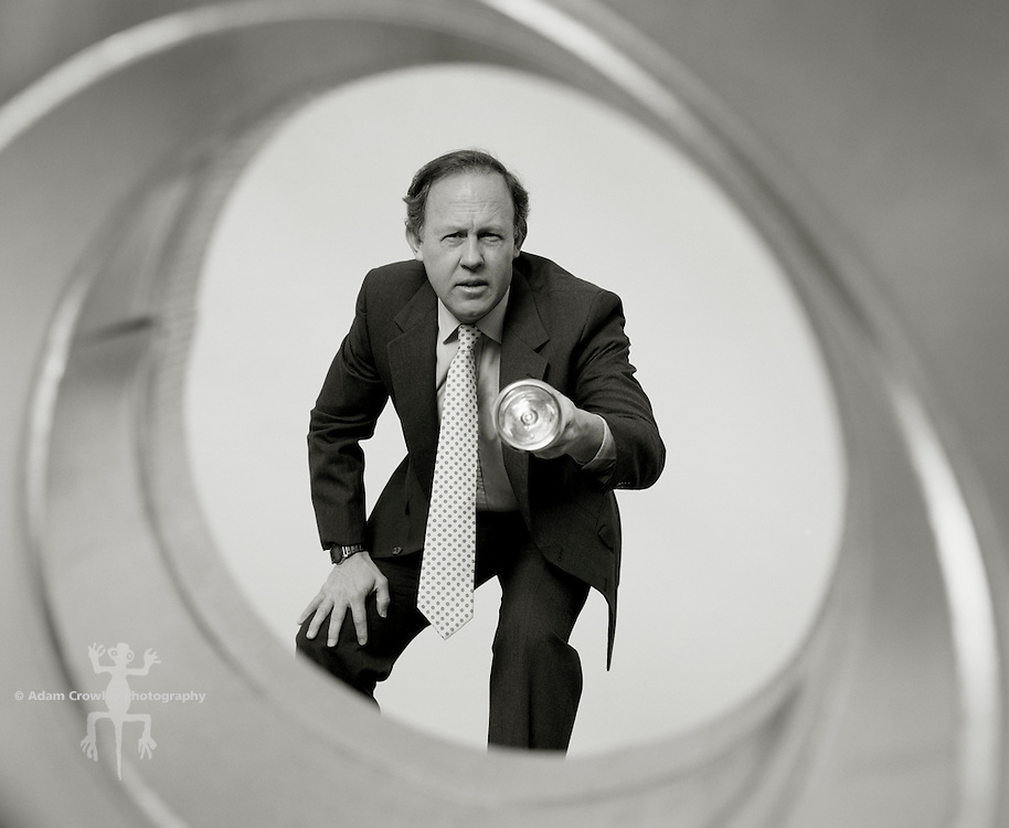 Businessman looking through pipe, with flashlight.