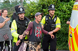 © Licensed to London News Pictures; 13/06/2020; Bristol, UK. A man is led away by police as new travellers face eviction from the old gas works site on Glenfrome Road continue to block the entrance with a caravan and occupy a contractor's JCB into the evening after bailiffs from GRC arrived on Saturday morning with police also in attendance who have closed off the road. The travellers have been living on the site, which is owned by Wales and West Utilities, for some weeks, and say that the eviction is illegal and is being done without any court papers. The travellers have been told that this is a common law eviction, but they say it is illegal because there is building on the land (hidden by foliage) which is permanently occupied and so the land is ancillary to the building and so a possession order must be granted by a court before an eviction can take place, and that no possession order has been granted. Photo credit: Simon Chapman/LNP.