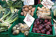 Vegetables on market stall for sale priced in sterling using pound weight