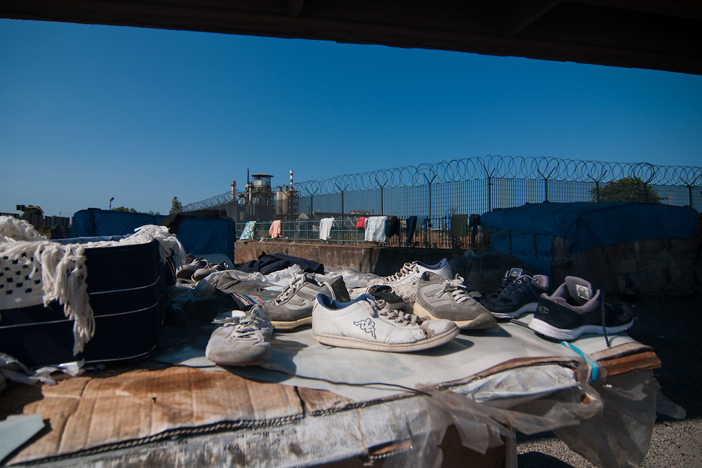 Shoes are drying on the sun in a camp of illegal migrants near the railway station on August 03, 2017 in Crotone, Italy. The city of Crotone hosts one of the biggest european centre for migrants, but some of them live in clandestinity, even for two years, in an area near the city railway station, because they are afraid to be rejected and to be sent to their nations again. ©Simone Padovani