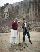A father and his son plant a cherry tree. In the old fortified village of Altit, over 1000 years old, Hunza region.