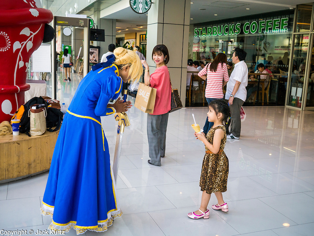 """30 MARCH 2013 - BANGKOK, THAILAND: A Thai teenager in a """"cosplay"""" outfit talks to a girl in the Central World Mall in Bangkok, one of the most upscale malls in Bangkok. Thailand's economic expansion since the 1970 has dramatically reduced both the amount of poverty and the severity of poverty in Thailand. At the same time, the gap between the very rich in Thailand and the very poor has grown so that income disparity is greater now than it was in 1970. Thailand scores .42 on the """"Ginni Index"""" which measures income disparity on a scale of 0 (perfect income equality) to 1 (absolute inequality in which one person owns everything). Sweden has the best Ginni score (.23), Thailand's score is slightly better than the US score of .45.   PHOTO BY JACK KURTZ"""