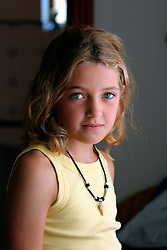 Portrait of serious looking girl aged 8 in natural light UK