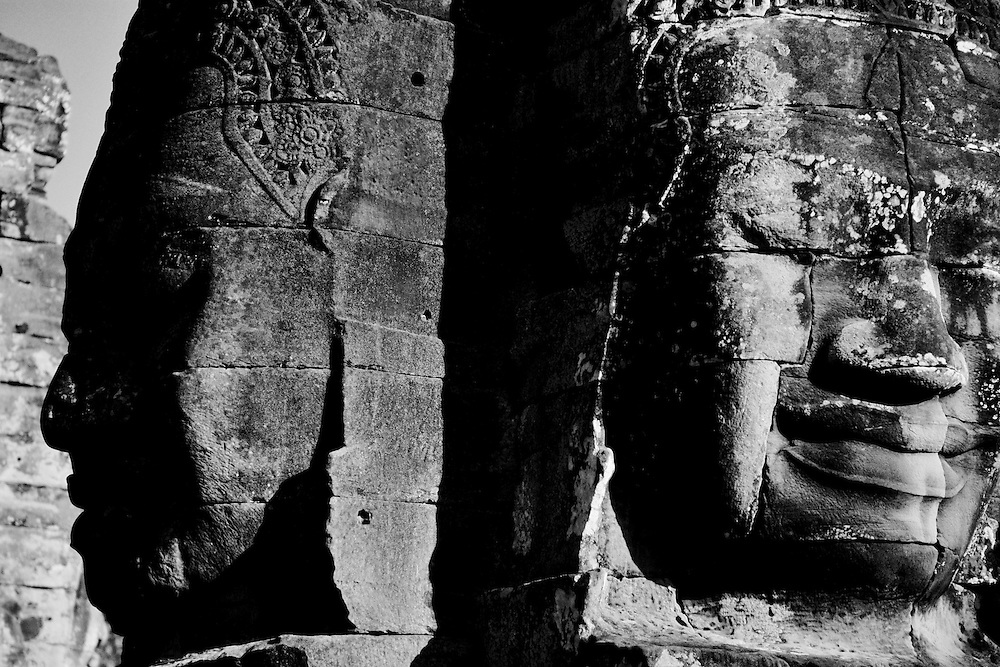 The smiling faces of Avalokiteshvara at the Bayon temple in Angkor Thom city shot in Black and White.<br /> <br /> The Bayon is the second most well known temple after Angkor Wat in the Angkor complex located at the center of Angkor Thom city.  The ruins of Angkor, a UNESCO World Heritage Site with temples numbering over one thousand, are hidden amongst forests and farmland to the north of the Tonle Sap Lake (Great Lake) and south of the Kulen Hills outside the modern city of Siem Reap, Cambodia.  Angkor served as the seat of the Khmer empire and flourished from approximately the 9th century to the 13th century. <br /> <br /> Built in the late 12th or early 13th century as the official state temple of King Jayavarman VII,  the Bayon temple is comprised of <br /> 54 towers with the smiling face of Avalokiteshvara.<br /> <br /> These Buddhist Saints or bodhisattva embody the compassion of all Buddhas and are a beautiful and powerful sight to behold. Exploring the Bayon was an amazing experience.