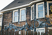 Melted vinyl siding peels off the walls of a residential building adjacent to the arson and destroyed buildings along Lake Street in Minneapolis, Minnesota on Monday, June 1, 2020.
