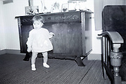little girl standing in front of commode with framed old family images 1960s