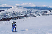 Snow Border hiking across snowy landscape, backpack, white, blue sky