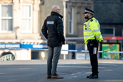 © Licensed to London News Pictures. 27/02/2019. London, UK. A crime scene investigator speaks with a police officer at the scene outside Ilford Station, where a 20-year-old man was fatally stabbed last night. A murder investigation has been launched. Photo credit: Rob Pinney/LNP