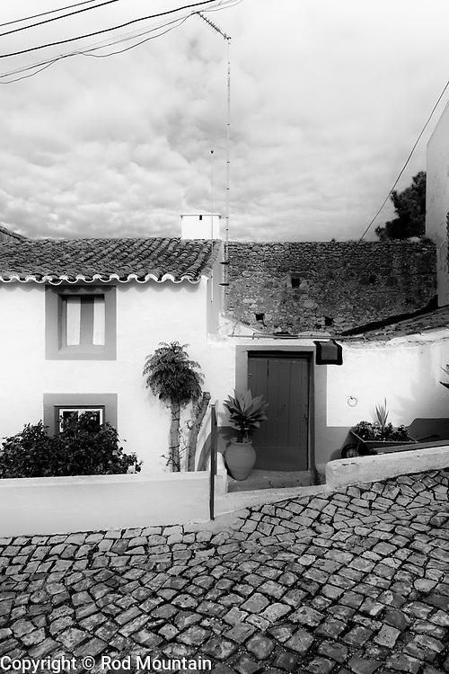 A humble abode not far from a popular lookout area overseeing Nazare and beach.<br />  <br /> https://en.wikipedia.org/wiki/Nazaré,_Portugal<br /> https://www.visitportugal.com/en/node/73770<br /> <br /> Image: © Rod Mountain<br /> www.rodmountain.com<br /> <br /> https://rodmountain.photoshelter.com/gallery/Nazare-Black-and-White/G0000SqXcaHZuxiQ/C00008zTgVT4bvvI<br /> <br /> #tourismportugal #portugal #visitportugal #portugal🇵🇹 #culturaportugesa <br /> #traveldeeper<br /> #suitcasetravels<br /> #letsgosomewhere<br /> #welltravelled<br /> #travelmemories<br /> <br /> #turismoemportugal #turismo #stayandwander #bnw_planet<br /> #blackandwhiteisworththefight<br /> #wonderlust.portugal #paperjournalmag #foammagazine #rentalmag #documentyourdays<br /> <br /> #monochrome<br /> #blackandwhitephotography<br /> #bwphotography<br /> #instablackandwhite<br /> #blackandwhiteart<br /> #Nazare #HomeSweetHome <br /> <br /> @visitportugal