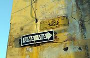 Street signs for Calle de Sto Domingo and Una Via, One Way.. Antigua Guatemala, Republic of Guatemala. 02Mar14