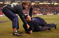 Photo. Daniel Hambury.<br /> Chelsea v Liverpool.<br /> <br /> Carling Cup Final.<br /> 27/02/2005<br /> A Liverpool fan is taken away after invading the pitch.