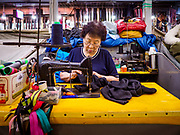 14 JUNE 2018 - SEOUL, SOUTH KOREA: A woman works at her sewing machine in Namdaemun Market. Namdaemun Market is one of the oldest continually running markets in South Korea, and one of the largest retail markets in Seoul. The streets in which the market is located were built in a time when cars were not prevalent, so the market itself is not accessible by car. The main methods of transporting goods into and out of the market are by motorcycle and hand-drawn carts. It occupies many city blocks, which are blocked off from most car traffic due to the prevalence of parking congestion in the area.       PHOTO BY JACK KURTZ