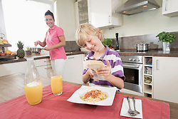 Boy grating cheese over spaghetti while his mother cooking food, Bavaria, Germany