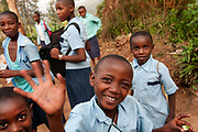Rwanda February 2014. Kigali. <br /> Children coming home from schoollaughing and smiling.