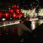 A couple kissing in front of christmas decorations on 6th Avenue, Manhattan, New York USA. 25th November 2012. Photo Tim Clayton