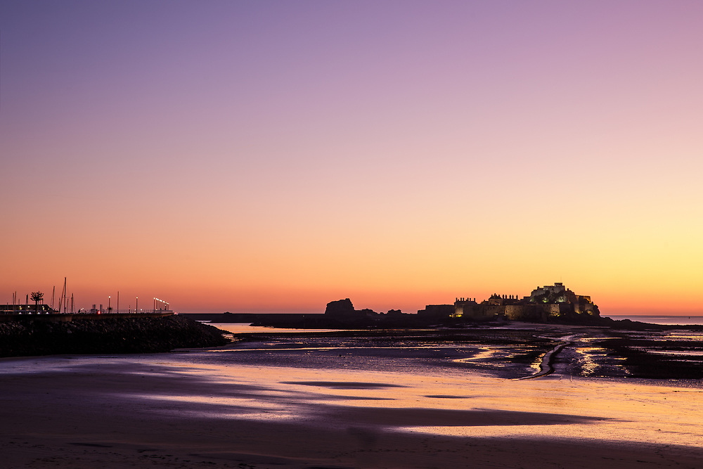 Orange pink skies reflecting in the sand at sunset at Elizabeth Castle, the tourist attraction and historic heritage site in Jersey, Channel Islands