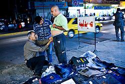 Men shop for pants on the sidewalks in Karadah district, Baghdad in Iraq.