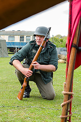 Members of 4 Kompanie Großdeutschland take part in the first days battle re-enactment at Fort Paull. A reenactor crouches looking for a target <br /> <br />   03 May 2015<br />   Image © Paul David Drabble <br />   www.pauldaviddrabble.co.uk