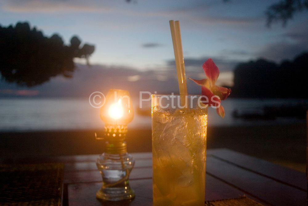 Lychee juice drink with straw and orchid flower sits on a table lit by an oil burner at sunset on Railay West Bay, Railay.