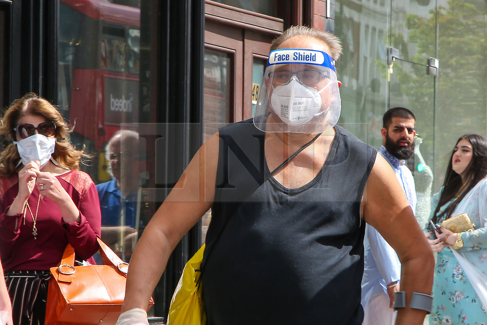 """© Licensed to London News Pictures. 24/05/2020. London, UK. A man wearing a visor walks past a Turkish restaurant on Green Lanes, Haringey in north London which is open for take away only due to coronavirus lockdown, as Muslims celebrate Eid al-Fitr.  On Eid al-Fitr also known as """"Festival of Breaking the Fast"""", a religious holiday celebrated by Muslims worldwide that marks the end of the month-long fasting of Ramadan, restaurants would normally be packed with people celebrating Eid. Photo credit: Dinendra Haria/LNP"""
