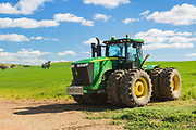 John Deere 9410R four-wheel drive (4WD) tractor in farm pasture paddock under cumulus cloud near  Woodstock, New South Wales, Australia. <br /> <br /> Editions:- Open Edition Print / Stock Image