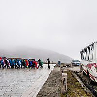 In the rain and led by a red flag, North Korean citizens leave their bus to begin to hike up Mount Paektu, the most sacred and revered place in North Korea.