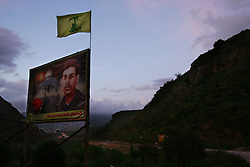 A martyr poster of Haysam Dbouk adorned with a Hezbollah flag is seen at the site where he blew himself up in 1989 in the mountains of Talinahas, Lebanon, March 10, 2005. Earlier in the week hundreds of thousands of pro-Syrian protesters answered the nationwide call from Hezbollah, the militant Shiite Muslim group, to demonstrate against foreign intervention.