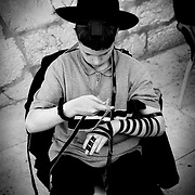 Young haredím putting on the leather straps that hold the phylacteries containing extracts of the Pentateuco.Muro of the Lamentations. Jerusalem.Israel.