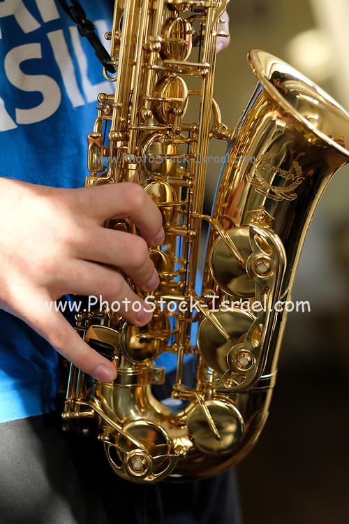 Closeup of a young boy playing a saxophone