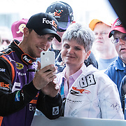 Driver Denny Hamlin is seen taking a selfie with a fan in the garage area during the last practice session for the 57th Annual NASCAR Daytona 500 race at Daytona International Speedway on Saturday, February 21, 2015 in Daytona Beach, Florida.  (AP Photo/Alex Menendez)
