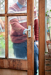 Opening the greenhouse door on a mild winter's day for ventilation
