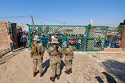 JOHANNESBURG, SOUTH AFRICA - MAY 08: SANDF members monitor people gathering at a food distribution centre in Diepsloot on May 08, 2020 in Diepsloot, South Africa. In partnership with with government and Celebration Church, Engen Fuel Retailers contributed food parcels for over 4000 familes in Diepsloot during lockdown level 4. (Photo by Dino Lloyd)